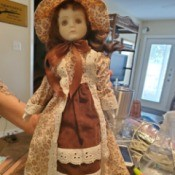 Identifying a Porcelain Doll - doll wearing long dress of brown and floral fabric with eyelet lace trim and matching hat