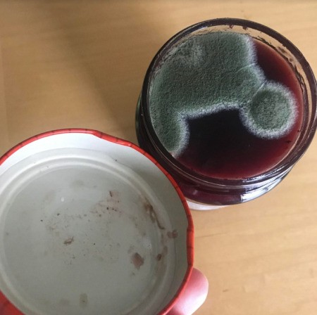 A jar of jam that is moldy.