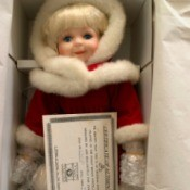 Value of a Dynasty Porcelain Doll - doll in box wearing a red coat with white fur trim