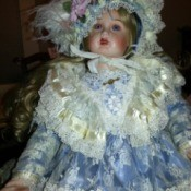 Identifying a Porcelain Doll - doll wearing ice blue dress and matching hat with lots of lace trim
