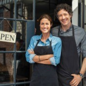 """A couple next to an """"Open"""" sign on a business."""