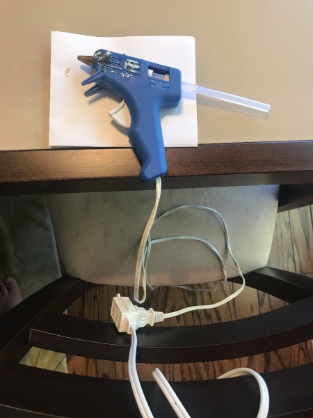 Stop Hot Glue from Slipping Off Table - glue gun attached to an extension cord wrapped around chair back