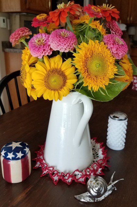 Zinnias and sunflowers in a white pitcher.