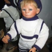 Identifying a Porcelain Doll - boy doll wearing a blue and white sweater and leggings