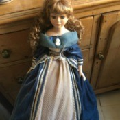 Identifying French Porcelain Dolls - doll with hair in long ringlets wearing a blue dress with white underskirt