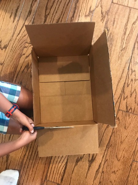 Cutting cardboard boxes for as art supplies.