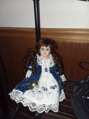 Value of an Ashley Belle Doll - doll wearing a white lacy dress with a dark blue overskirt