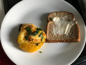 Baked Egg in a Tomato on plate with bread slice