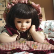Identifying a Porcelain Doll - doll in gingham dress lying on tummy and propped up on elbows