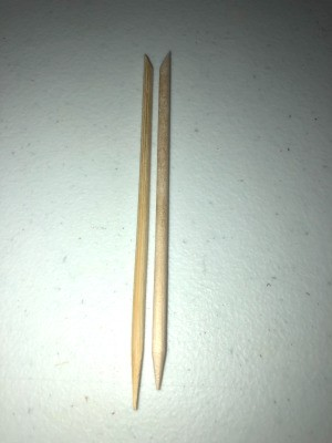 A homemade bamboo cuticle stick next to a store bought one.