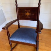 Identifying an Antique Rocker - dark wood rocking chair with decorative design on backrest and tall finials