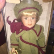 Value of a Collector's Choice Porcelain Doll - doll wearing a green coat with plum trim and matching hat