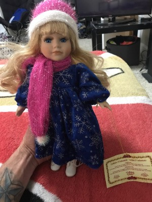 Value of a Collector's Choice Doll - doll wearing a pink and white knit hat and scarf with a dark blue dress with snowflakes
