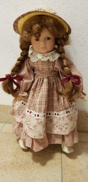 Identifying a Porcelain Doll -doll with braids and a straw hat
