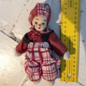Identifying a French Porcelain Doll - little clown doll wearing red shirt and plaid pants and matching hat