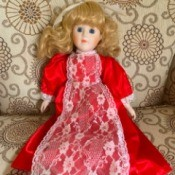 Identifying a Porcelain Doll - doll in red dress with lace apron
