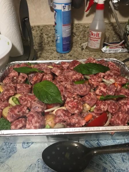sausage on top of veggies in baking pan