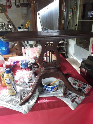 Value of a Vintage Lyre Table - table on newspapers being cleaned
