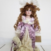 Value of a Collectible Memories Porcelain Doll - doll with long red hair wearing a period ecru lace and lavender satin dress and hat