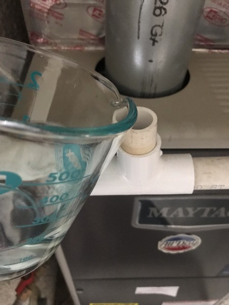 Pouring water into the AC condensation tube.