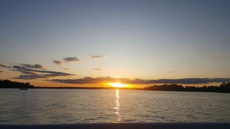 The sun setting over a large lake.