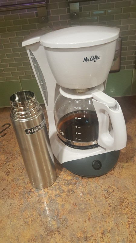 A coffee pot next to a stainless steel travel mug.