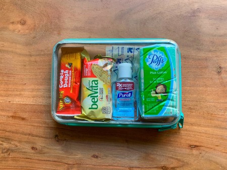 A clear container storing emergency supplies for a child going to school.