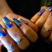 Long nails beautifully manicured with an opalescent blue polish.