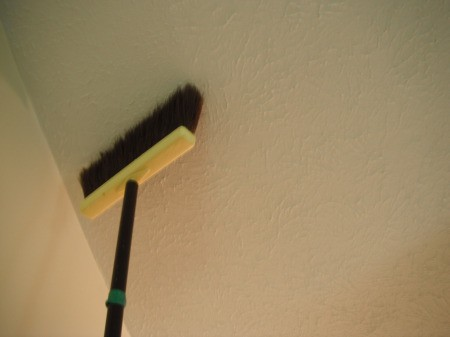 Cleaning a Bedroom By Yourself - dusting ceiling with a broom