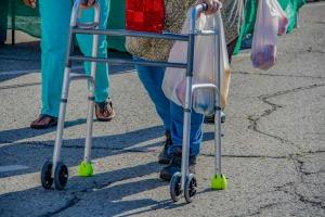 A woman using a walker on a street.