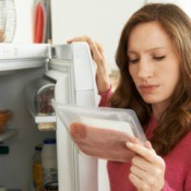 A woman looking at a package of meat from the fridge.