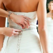 Measurements being taken of a woman in a wedding dress.