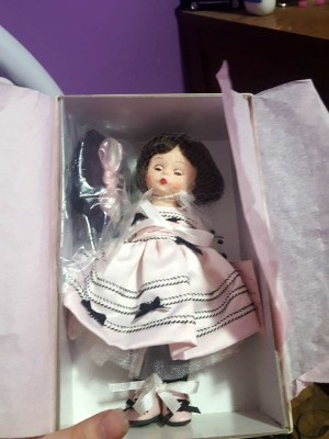 Value of a Madame Alexander Doll -  small doll with closable eyes wearing a white dress with dark trim and bows