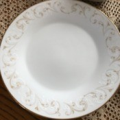 Value of Noritake China - white plate with a gold and white scroll pattern