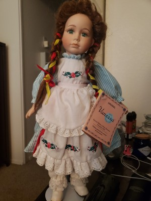 Identifying a Vanessa Porcelain Doll - doll with braids, a striped dress and white lace edged, embroidered apron