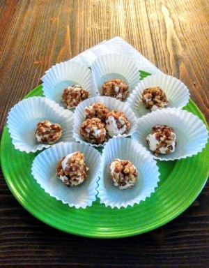 A plate of pecan log balls served on white liners.