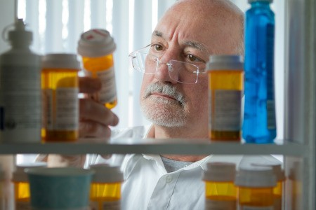 A man looking at his prescriptions in a medicine cabinet.