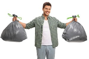 A man holding two bags of trash.