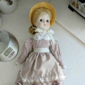 Identifying a Porcelain Doll - doll wearing a straw bonnet, and a dusty rose colored long dress with eyelet trim