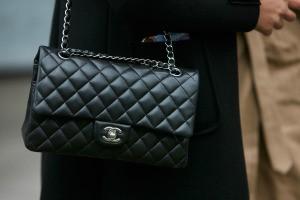 A woman holding a Chanel handbag.