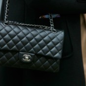 A woman holding a Chanel handbag.