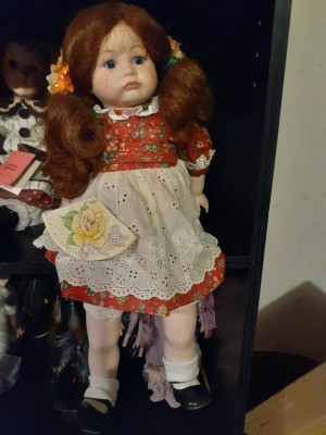 Value of a Victoria Ashlea Porcelain Doll - doll wearing a red print dress with an eyelet apron