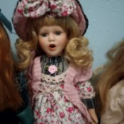 Identifying a Porcelain Doll - doll wearing plaid dress with floral jumper and matching hat