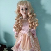 Identifying a Porcelain Doll - doll with long blond ringlets wearing a peach dress with white lace trim