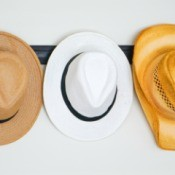 A collection of hats hanging on a wall coat rack.
