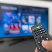 A remote in front of a television screen.
