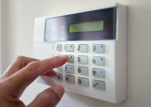 Fingers pressing buttons on an alarm system.