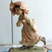 Value of an Armani Figurine - figurine of a little girl wearing a long dress and ruffled brimmed hat running