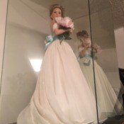 Value of an Ashton Drake Doll - doll wearing a long white dress with a blue sash in a clear doll display case