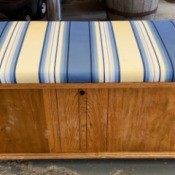 Value of a Lane Cedar Chest - medium wood finish chest with blue, black, white, and yellow striped cushion